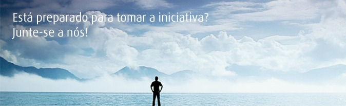 Picture of man standing in a panoramic landscape with a cloudy sky. Translated to Portuguese.